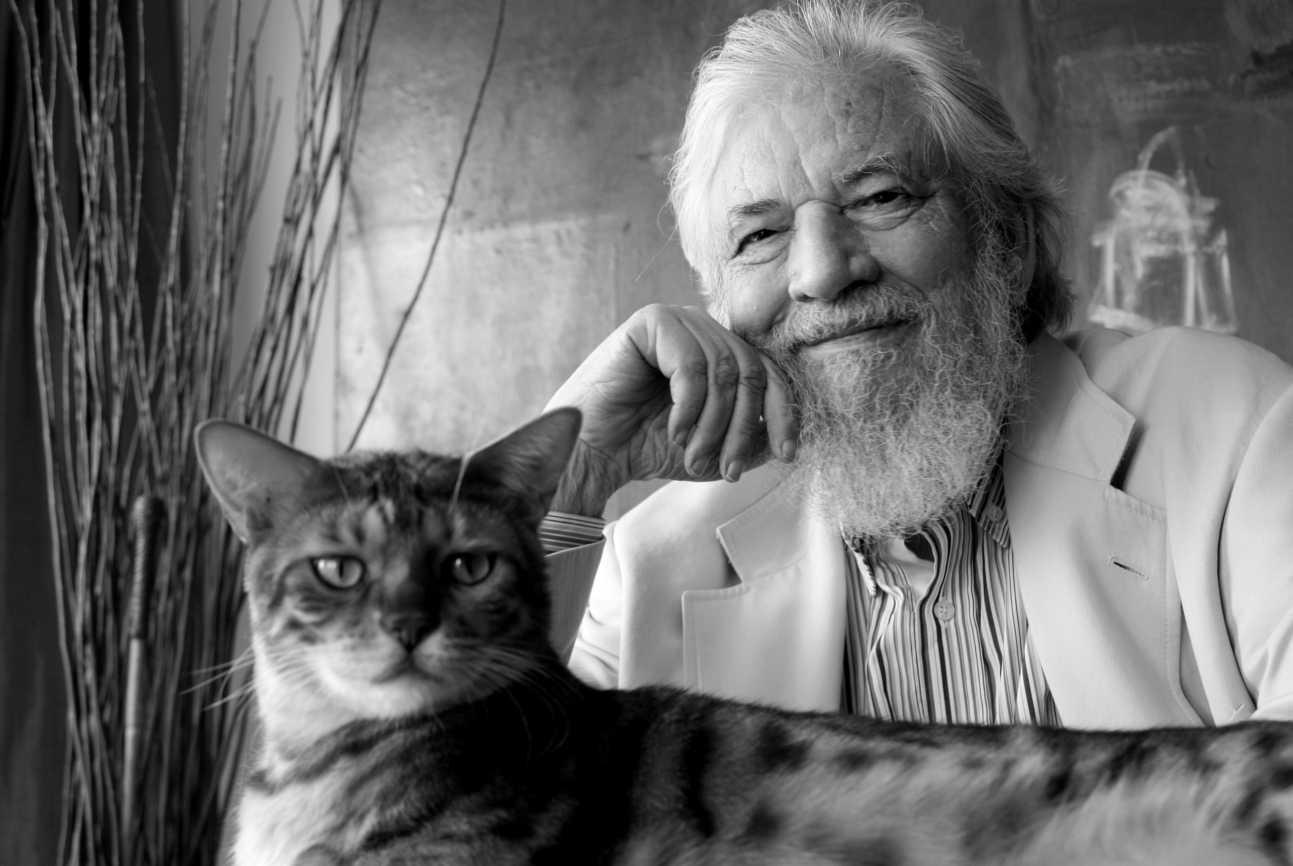 Naranjo sorride e il gatto guarda in camera
