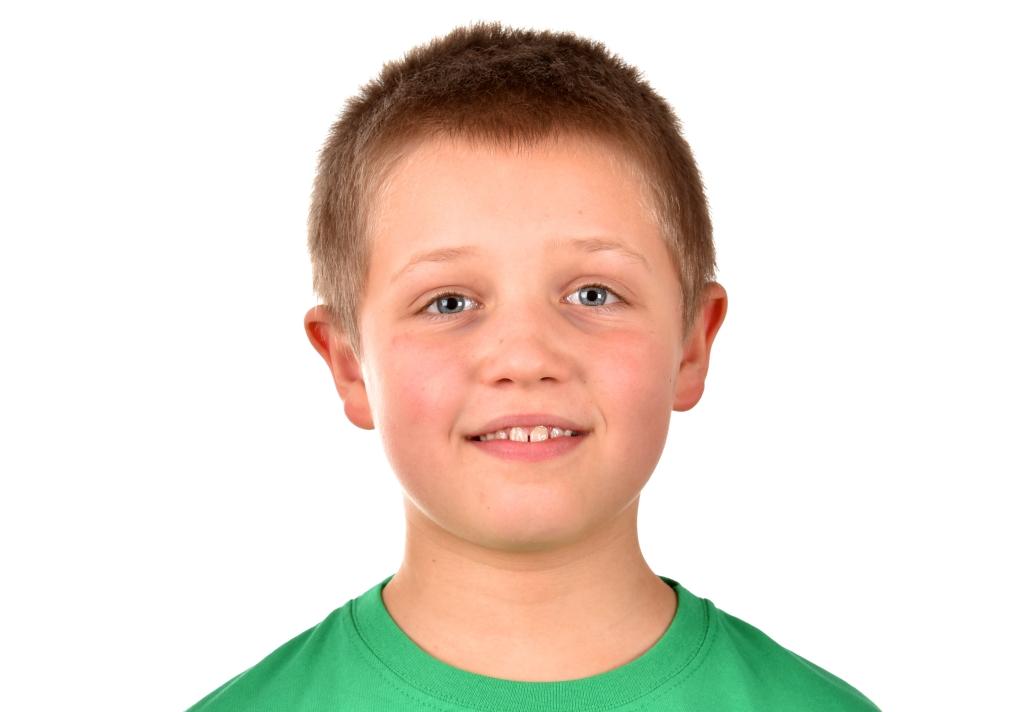 un bambino con l'espressione innocente, occhi azzurri maglietta verde