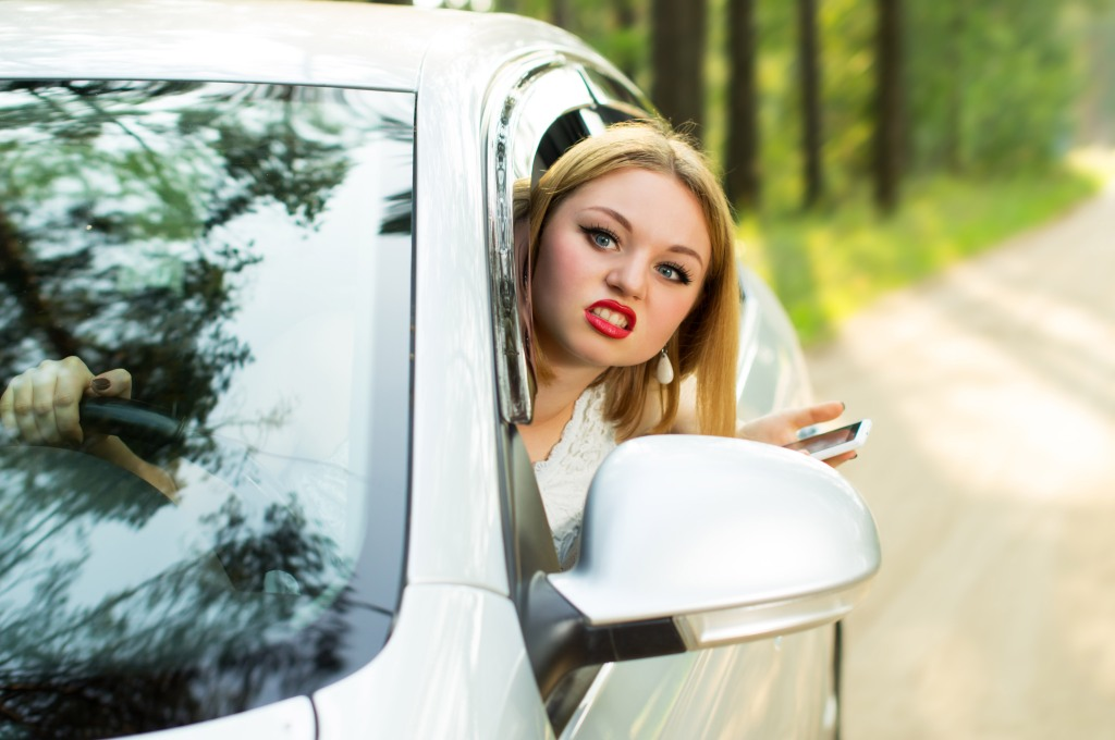con lo smartphone in mano, ragazza bionda con rossetto e faccia schifata , sporge con la testa dal finestrino dell'auto