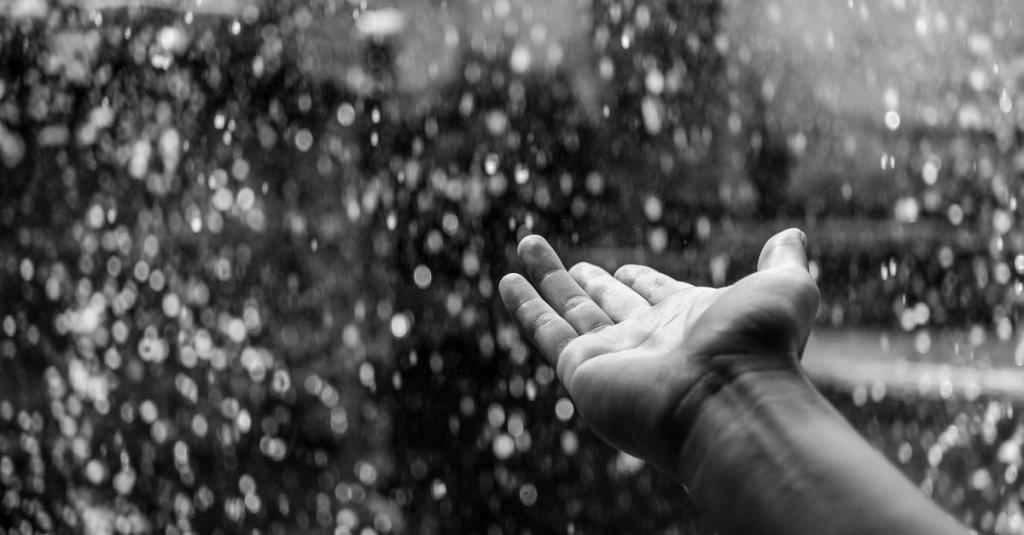 foto in bianco e nero di una mano tesa e la pioggia sullo sfondo